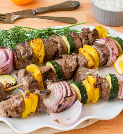 skewers with lamb, red onion, and yellow bell pepper on them