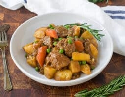 lamb, potatoe, carrots, and peas in a white bowl with a sprig of rosemary garnish