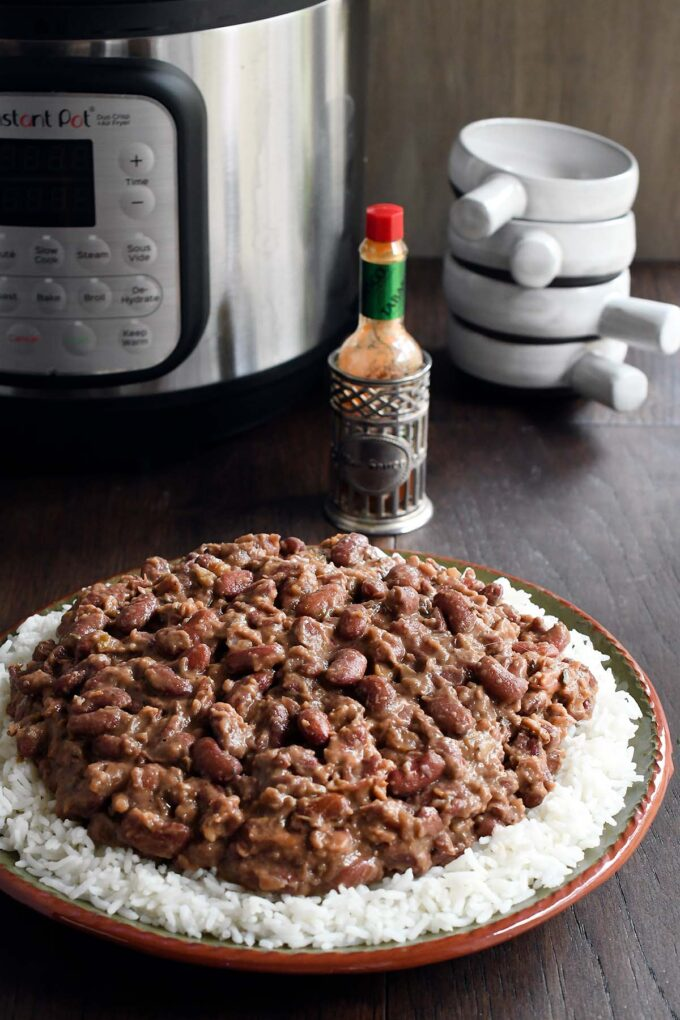Plate of red beans over white rice in front of an instant pot.